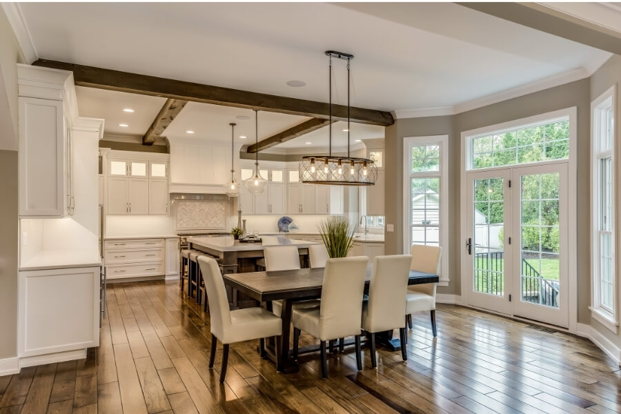 White kitchen with sculptural pendant lighting and recessed lighting