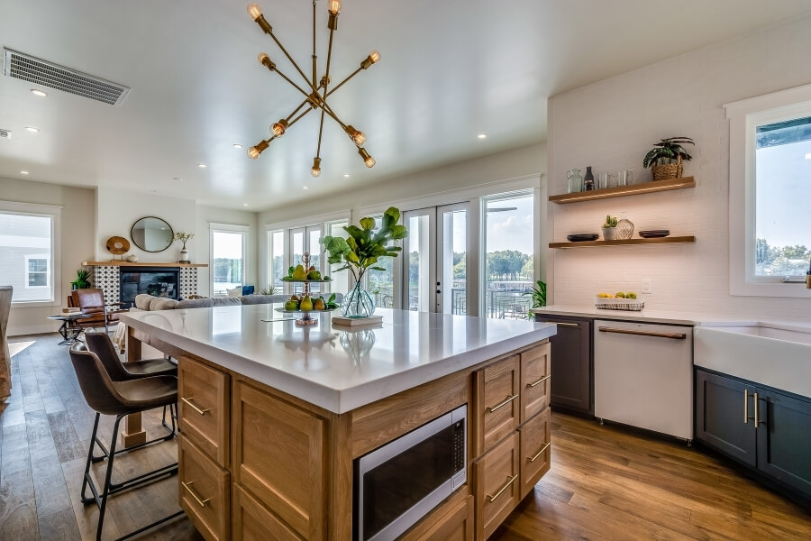 geometric chandelier over kitchen island in a modern kitchen open concept with family room
