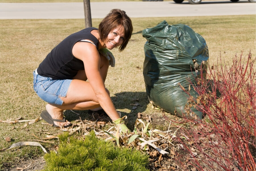 Woman cleaning debris from yard