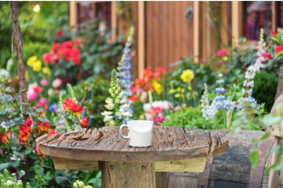 Wood table with coffee cup in flower garden